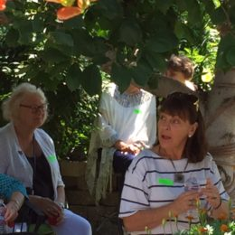 Gwen Clancy and others in the garden listening to Emma George